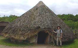 Henry beside reconstructed Neolithic Hut